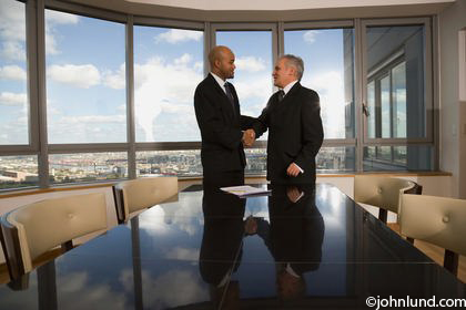 Top executives are shaking hands in this picture of a business meeting between two mature businessmen. Behind the two men shaking hands are a bunch of big windows with a great view of interesting cloud formations.